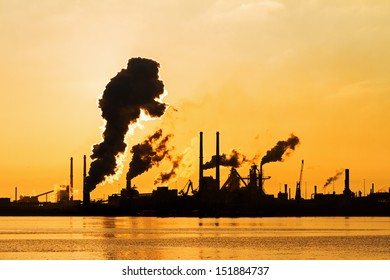 Sunset view of the heavy industry with smoking chimneys in IJmuiden, the Netherlands
