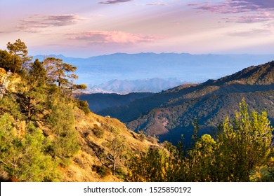 Sunset view of hills and valleys in the Santa Cruz mountains; South Clara Valley and Diablo mountain range visible in the background