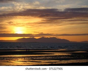 Sunset view of Isle of Arran taken from the Ayrshire coast at Prestwick at low tide.