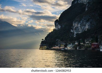 Sunset view of Lake Garda, Italy. The sun beams are shinning through the coastal cliffs of Riva del Garda. Some colourful residences are visible along the coast near the water