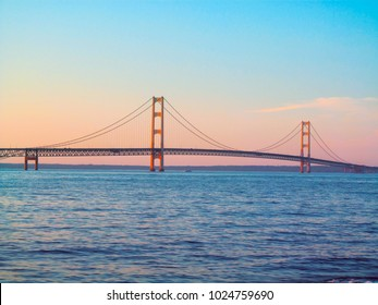 Sunset view of the Mackinac Bridge in Michigan, USA. This is a long steel suspension bridge located in the Great lakes region. It is one of the most famous landmarks of North America.