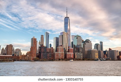 Sunset view of Manhattan skyline from city river, New York City.