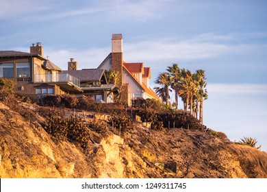 Sunset view of mansions built on top of cliffs on the Pacific Ocean coast, Malibu, Los Angeles county, California