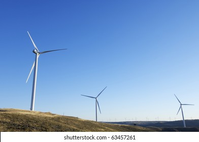 sunset view of modern windmills on a hill