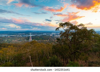Sunset view from Mount Ainslie Lookout. ANZAC Parade leading to the Australian War Memorial and then to the new and old Parliament Houses in the background. A tranquil scene.
