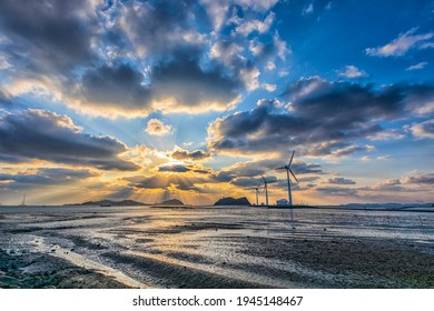 Sunset view of mud flat at Tando Port of Daebudo Island with the background of wind power generators near Ansan-si, South Korea