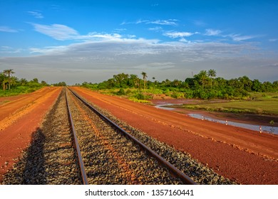 Sunset view of a newly laid section of rail track between Kamsar and Sangaredi in the west of the Guinea for the delivery of bauxite by mining shuttle trains. Guinea, Africa.