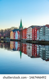 Sunset view of Nidaros cathedral and colorful timber houses surrounding river Nidelva in the Brygge district of Trondheim, Norway