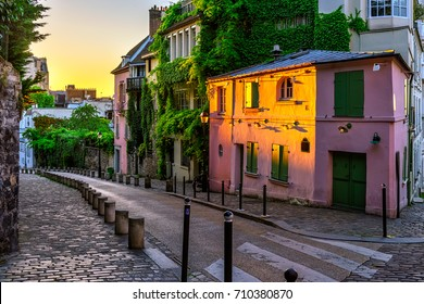 Sunset view of old street in quarter Montmartre in Paris, France. Cozy cityscape of Paris. Architecture and landmarks of Paris