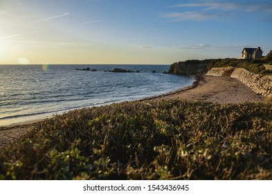 Sunset view on Atlantic shore beach. Path with green grass and long beach