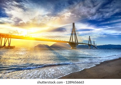 Sunset view on the bridge near Patras. Suspension bridge crossing Corinth Gulf strait, Greece, Europe. Second longest cable-stayed bridge in the world. Dramatic red sky under a Rion-Antirion Bridge.