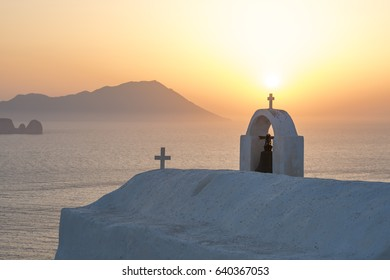 Sunset view on the island of Milos in Greece, with a small chapel in the foreground and the island of Antimilos in the distance.