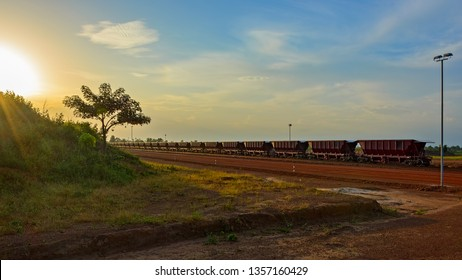 Sunset view to railway carriages for transportation of bauxite ore on train tracks at the end of the railway line from bauxite mining. Guinea, Africa.