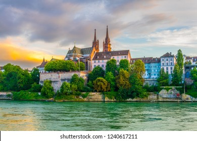 Sunset view of riverside of Rhine in Basel dominated by majestic building of Munster church, Switzerland