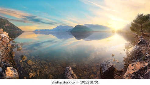 Sunset view from the rocky shore of a mountain lake. Panorama