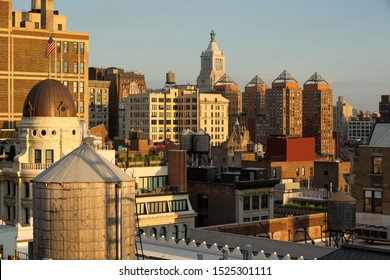 Sunset view of rooftops and penthouses of the Flatiron District. The elevated view showcases building facades with architectural ornaments and water towers. Manhattan, New York
