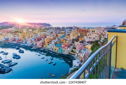 Sunset view of serene sea, fishing and sightseeing boats, cafes and restaurants in Marina Corricella, Procida Island, Italy.