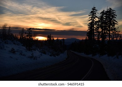 Sunset view from Shasta Road on Christmas day, snow covered slopes and pine trees, orange clouds above mountains and blue sky.