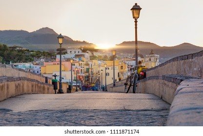 Sunset view from side of Aragonese Castle on Ischia street with colourful houses, Ischia Island, Italy. People blurred due to very long exposure time.