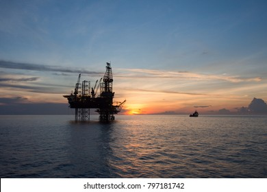 Sunset view with silhouette of an oil rig and a ship