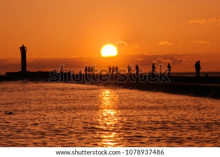 Sunset view with silhouettes of people fishing at baltic sea on Mangalsala pier in Riga