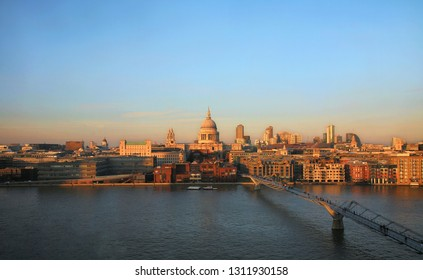 Sunset view of St Paul's Cathedral and Millennium Bridge seen from Tate Modern. Dramatic orange colored sunset view present over blue sky.