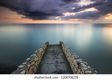 Sunset view from a stone pier overlooking storm clouds on the horizon