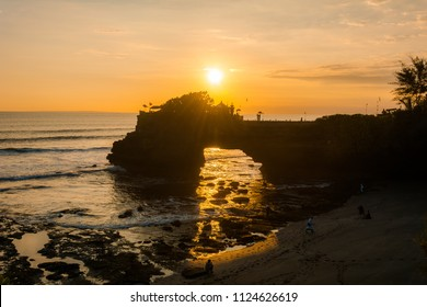 A sunset view from Tanah Lot Temple with a touris on the beach in Bali, Indonesia