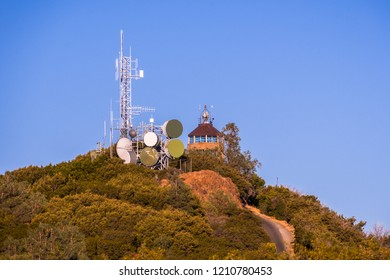 Sunset view of telecommunications antennas close to Mt Diablo summit; the building on top of Mt Diablo summit visible in the background; San Francisco bay area, Contra Costa county, California