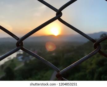 Sunset view through cage at Khun Dan Prakarn Chon Dam , Electrical generation dam