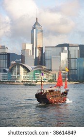 Sunset view of a traditional, junk ship with wind sails shot against modern cityscape of Hong Kong island