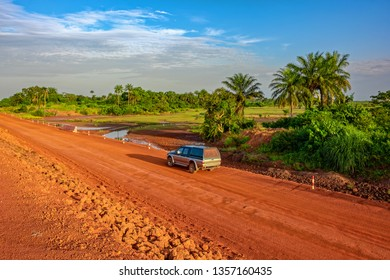Sunset view of a typical red soils unpaved rough countryside road along railway track in Guinea, West Africa.