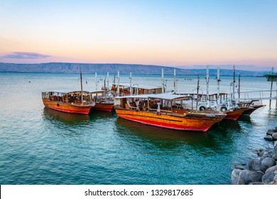 Sunset view of a wooden boat floating on the sea of galilee, Israel