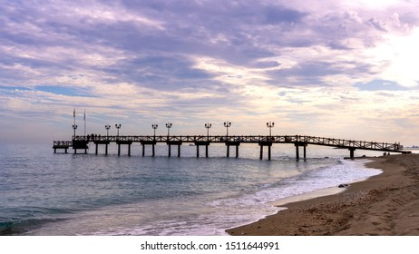 sunset view of wooden pier in marbella, located on golden mile. relaxing holiday view of romantic beach.