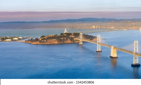 Sunset view of Yerba Buena Island and the Bay Bridge; the smoke plume from Kincade fire visible in the background; San Francisco, California