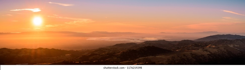 Sunset views of the south San Francisco bay area and the surrounding hills as seen from the top of Mt Hamilton; a thin layer of fog creates a soft orange colored light; San Jose, California