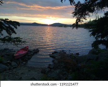 Sunset at Waldo Lake with trees framing picture and canoe on lake shore