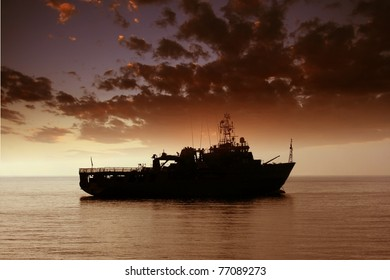 Sunset with warship anchored