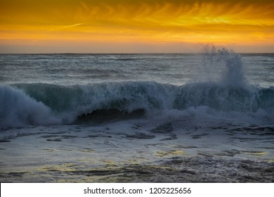 Sunset of a wave crashing onto the Carmel, California beach at sunset.