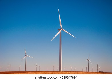 Sunset west Texas Wind Turbine Farm producing clean renewable and sustainable energy with large wind turbines in rows