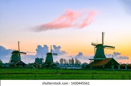 Sunset windmill farm in Holland. Windmills sunset silhouettes. Sunset windmill farm silhouette. Sunset windmill farm landscape