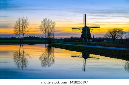 Sunset windmill farm river reflection. Sunset windmill river reflection. Windmill sunset river reflection. Sunset windmill river water reflection