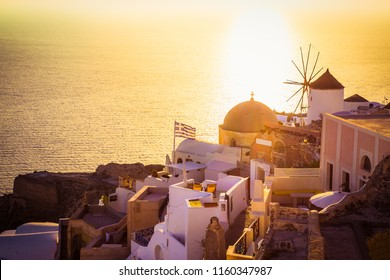 Sunset with windmill in Oia village on Santorini island, Greece.