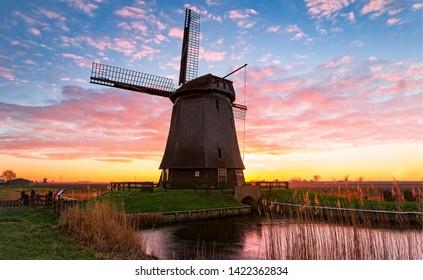 Sunset windmill river sky clouds. Windmill farm river sunset view. Sunset windmill farm scene. Windmill silhouette sunset sky clouds