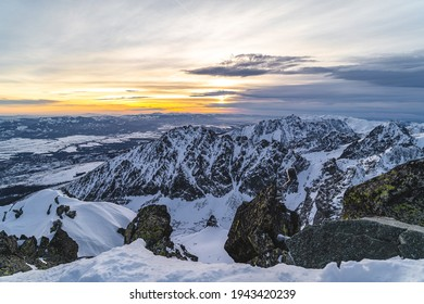 Sunset in winter alpine like mountain landscape of High Tatras, Slovakia. Snow covered mountains, high rocky faces and peaks during sunset.