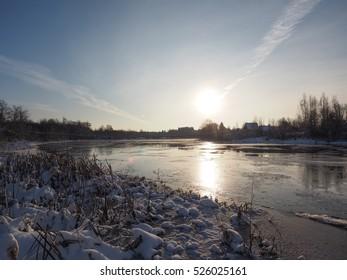 Sunset in winter. Winter river, fog. Russia. Rural landscape