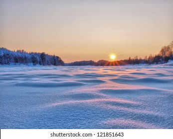 Sunset in winter. Winter rural landscape with the river at sunset.