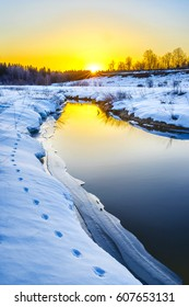 Sunset in winter. Trace of a fox along the river