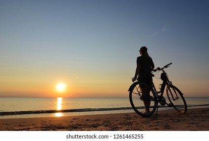 The sunset. Woman with the bicycle on the seaside