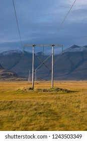 Sunset and wooden poles with power lines with Icelandic landscape in the background. Iceland